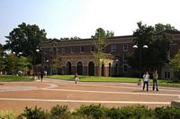 A modern 2 story brick building with students walking across a brick courtyard toward it.