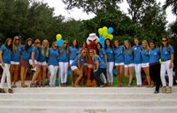 a couplke of dozen tri delts pose with the Ibis school mascot.