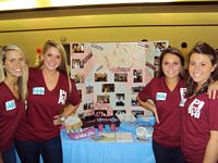4 lovely Pi Phis are manning a booth at the charity fair.