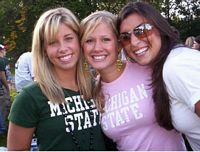 3 sexy gals in MSU t shirts are smiling at you.