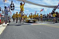 Here the MU solar car crosses the finish line to cheers of students all in yellow t shirts.