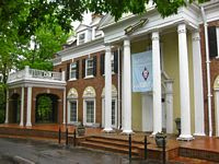 The Pi Phi house is a brick mansion with white round pillars and black shutters.
