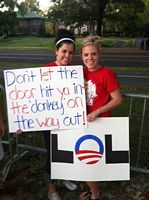 2 cute coeds hold up anti-Obama sign.