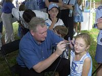 A man paints a little girl, in a Carolina cheerleader outfit, with a tar heel.