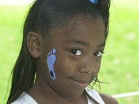 This young girl has a blue foot with a tar heel painted on her face.