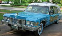 This classic Cadilac hearse is painted tarheel blue and white with all the logos etc.