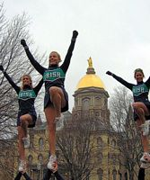 Three ND coeds are cheerleaderfs in this photo and being lifted high.  The gold dome and a fall sky are in the background.