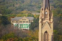 A view, from high up in the domed building.  The dorm is almost completely covered with a sign that says Go Irish in green letters on a white background.