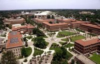 This is an aerial view of the main quad of grass criss crossed by concrete walks and surrounded by brick buildings with tile roofs.