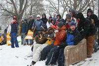 Pictured, during a snow storm, are students sledding, here using a couch with runners as a sled.