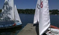 Purdue's sailing teams boats are shown here against blue waters and a sky with cluds that set off its blueness.