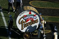 This is a scene where the band is towing the world's largest drum into the endzone.  The drum has the Macey's Parade Logo as they had just finished it when the game was played.