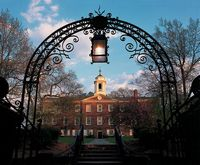 This iron ornamental gate has a lantern hanging from its center and marks the entrance to old Queens College.