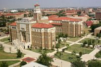 This aerial shot of the center of campus shows 4 story tall brick buildings with peaked red tile roofs.
